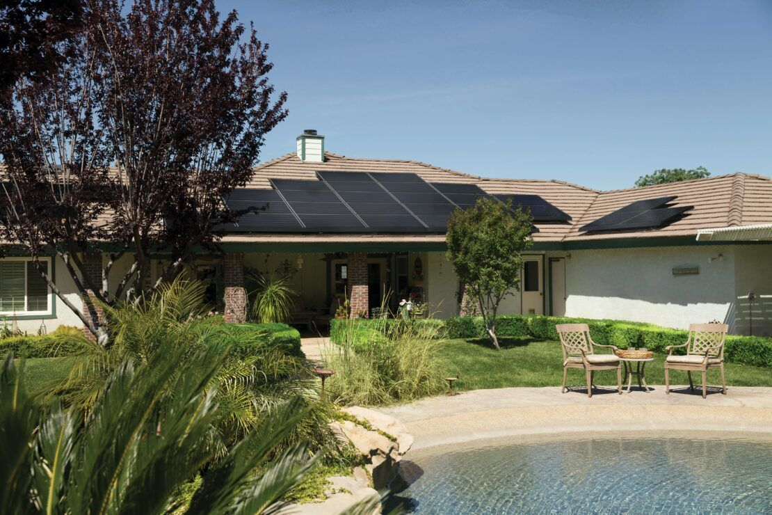 Foto de uma casa com placas solares instaladas no telhado. Amplo jardim, com referências sustentáveis.